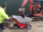 Electric powered Wheelbarrow being loaded by mini-digger