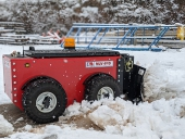 Radio-controlled MUV 4WD with plough attachment clearing snow
