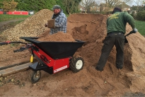 Electric powered Wheelbarrow being loaded with sand